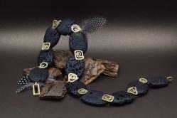 Een handgemaakt collier van lavasteen en 18 karaat geelgoud